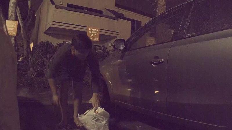 A vandal slashing a tire of a Tesla Model 3