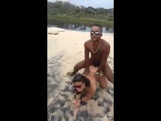 Негр задорно трахает раком двух телок по очереди на пляже